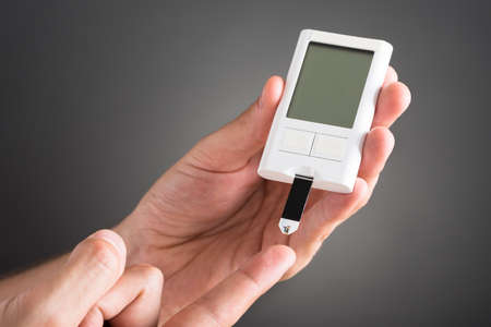 diabetes: Primer plano de la persona Manos Comprobaci�n de Sangre Nivel de Az�car Con Gluc�metro Foto de archivo