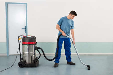 routine: Young Happy Male Worker Cleaning Floor With Vacuum Cleaner