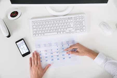 デスク カレンダーの重要な日付をマークする実業家のハイアングル
