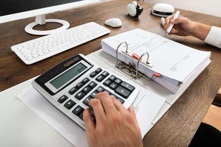 calculadora: Primer plano del hombre de negocios Factura Comprobación Con la calculadora en el escritorio