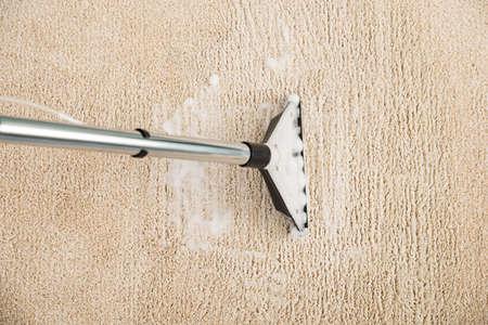 Vista elevada de la aspiradora eléctrica sobre la alfombra Con Espuma Foto de archivo