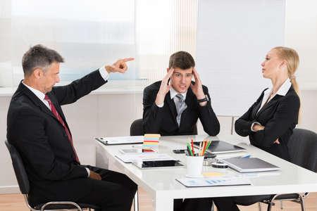 jefe enojado: Empresario maduro Discutir con sus dos compañeros de trabajo en la oficina