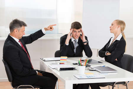 quarrel: Mature Businessman Arguing With His Two Co-workers In Office