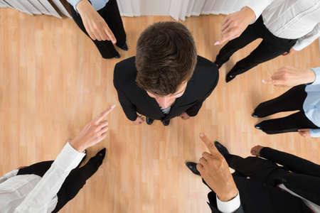 falta de respeto: Vista elevada de empresarios Equipo apuntando al empresario Foto de archivo