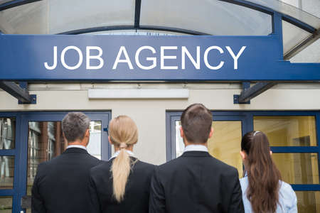 Rear View Of Businesspeople Standing Outside Job Agency Stock Photo