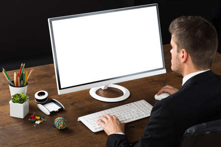 pencil holder: Young Businessman Working On Desktop Computer At Wooden Desk Stock Photo