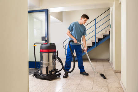 Happy Male Worker Cleaning Floor With Vacuum Cleaner Appliance Stockfoto