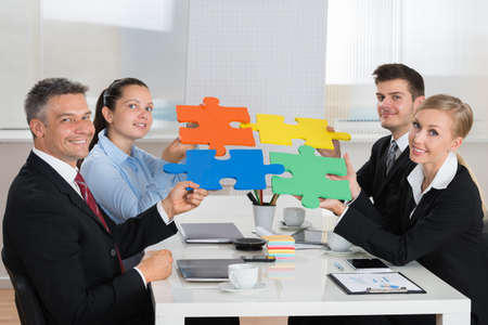 business puzzle: Happy Businesspeople Joining Multicolored Puzzle Piece In Meeting Stock Photo