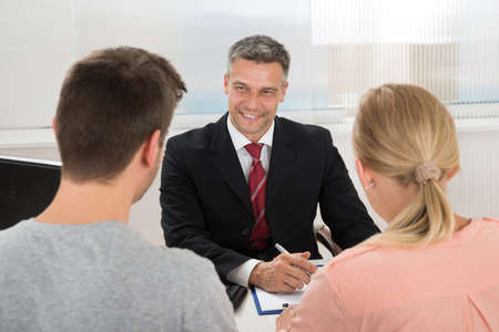 couple talking: Mature Happy Estate Agent Talking To Young Couple In Office Stock Photo