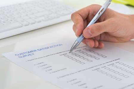 Close-up Of Person Hands Filling Survey Form With Pen Archivio Fotografico