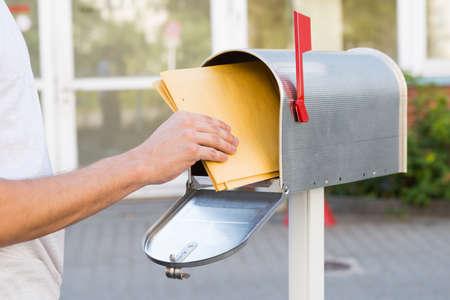 사서함에서 노란 편지를 제거하는 사람의 근접 스톡 콘텐츠