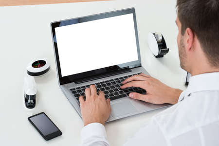 blank screen: Close-up Of Businessman Working On Laptop Showing Blank Display At Desk