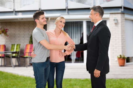 businessmen shaking hands: Mature Estate Agent Shaking Hands With Young Couple In Front Of House