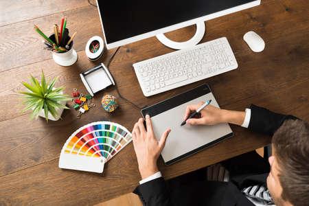 デスクで、スタイラスを備えたデジタル グラフィック タブレットを使用して若い男性デザイナー
