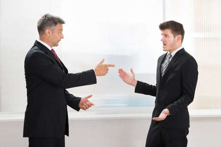 disagreeing: Two Businessmen Quarreling With Each Other In Office