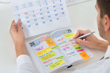 Close-up Of Businessman With Calendar Writing Schedule In Diary