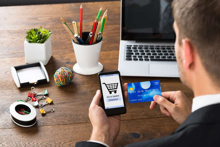 purchases: Close-up Of Businessperson Shopping Online With Mobile Phone And Credit Card