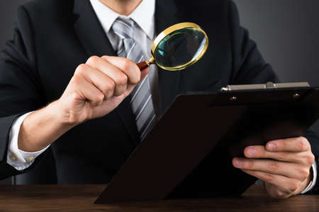 Close-up Of Businessperson Inspecting Document On Clipboard With Magnifying Glass