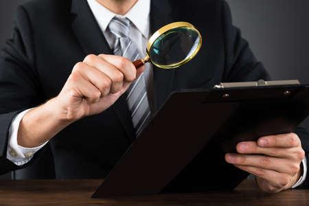 lupa: Primer De Empresario Inspección documento en el Portapapeles Con La Lupa