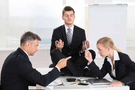 Two Businesspeople Quarreling In Front Of Businessman Meditating At Desk Foto de archivo