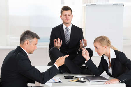 Two Businesspeople Quarreling In Front Of Businessman Meditating At Desk Imagens