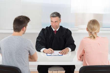 divorce: Juez Hombre maduro que se sienta delante de la joven pareja en la Sala Foto de archivo