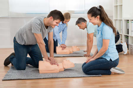 first class: Group Of Students Learning Cpr On Dummy In Class