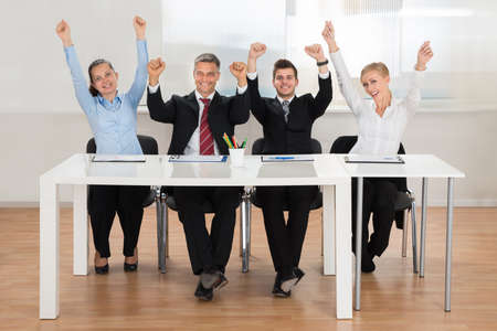 committee: Group Of Excited Businesspeople Raising Hands In Office