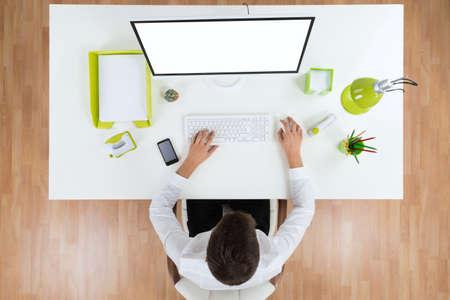 monitor de computadora: Vista elevada del hombre de negocios Trabajo En El Ordenador Mostrando Pantalla en blanco