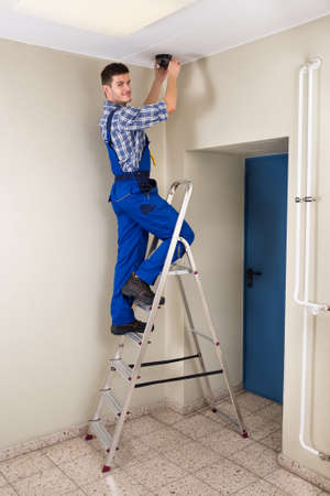 cctv camera: Male Technician Standing On Stepladder Fitting Cctv Camera