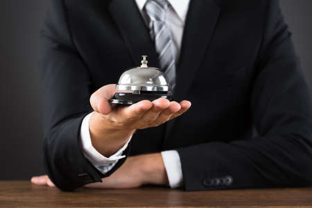 service desk: Close-up Of Businessperson Hands Holding Service Bell At Desk