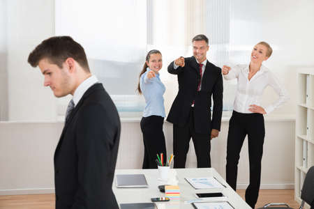 teasing: Happy Businesspeople Teasing Young Businessman Alone In Office