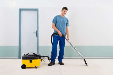 office appliances: Young Male Cleaner In Uniform Vacuuming Floor