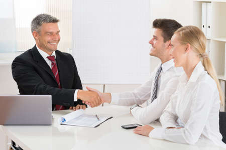 business finance: Estate Agent Shaking Hands With Young Happy Couple At Desk