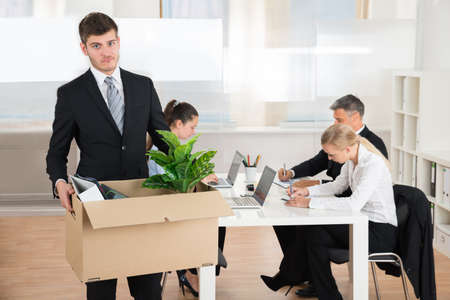 unemployed dismissed: Unhappy Businessman Carrying Belongings In Box While Other People Working In Office