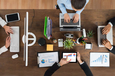 office supplies: High Angle View Of Businesspeople Working On Electronic Devices At Wooden Desk Stock Photo