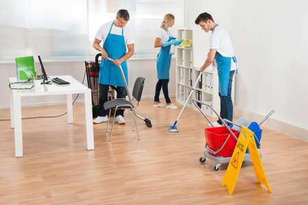 cleaning service: Group Of Three Janitors In Blue Apron Cleaning Office Stock Photo
