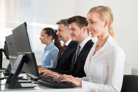 people on computers: Group Of Businesspeople Typing On Desktop Computer At Desk Stock Photo