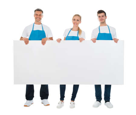 Group Of Cleaners Holding Blank Billboard Over White Background