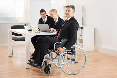 happy work: Happy Mature Businessman On Wheelchair With Colleagues In Office