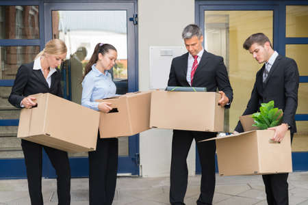Unhappy Group Of Businesspeople Standing With Cardboard Boxes Outside The Office