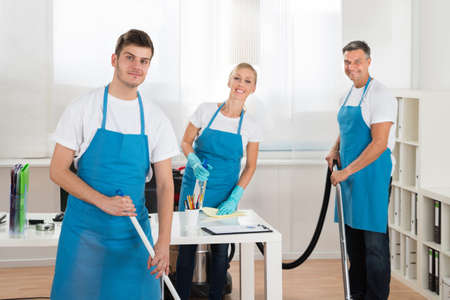 office uniform: Group Of Happy Janitors Cleaning Office With Cleaning Equipments Stock Photo