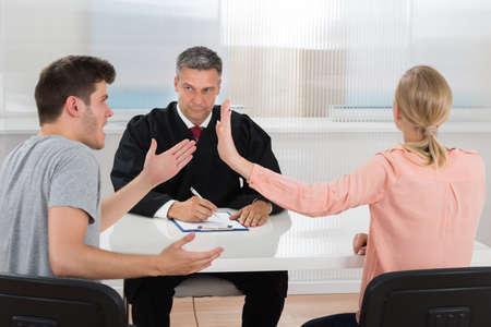 gente sentada: Pareja joven teniendo una discusión delante de la juez de sexo masculino en el escritorio