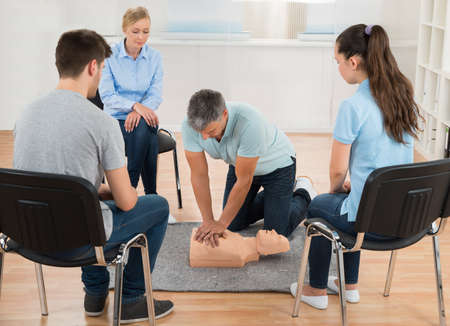 reanimate: Male Instructor Teaching First Aid Cpr Technique To His Students Stock Photo