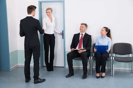 young businessman: Businesswoman Shaking Hands With Man In Front Of People Waiting For Job Interview In Office