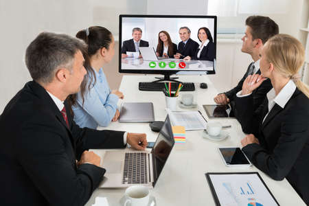 business conference: Group Of Businesspeople Watching An Online Presentation On A Desktop Computer In Office Stock Photo