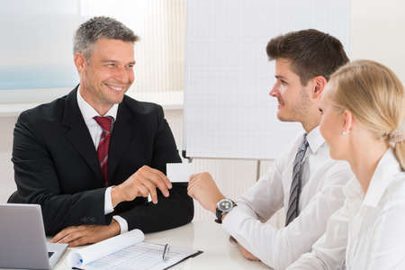 financial adviser: Male Consultant Giving Visiting Card To Young Couple In Office Stock Photo