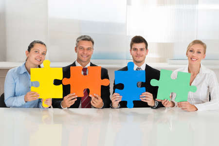 jigsaw puzzle pieces: Team Of Businesspeople Holding Four Multi-colored Puzzles At Desk
