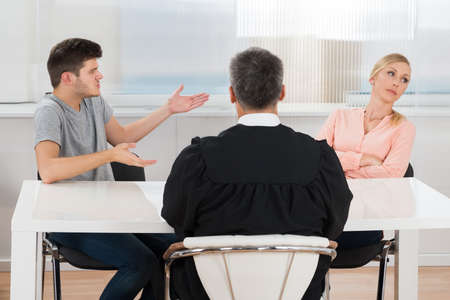 conflict: Rear View Of Judge Sitting In Front Of A Young Couple Having Conflict In Court