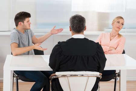 conflicto: Vista posterior del juez que se sienta delante de un par joven que se Conflicto en la Corte